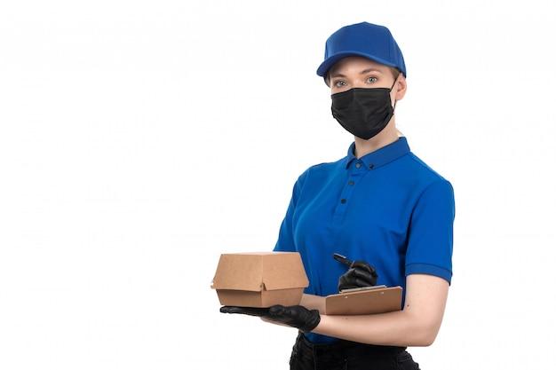 Uma jovem mensageira de frente com uma máscara preta de uniforme azul e luvas segurando um pacote de entrega de comida e um bloco de notas