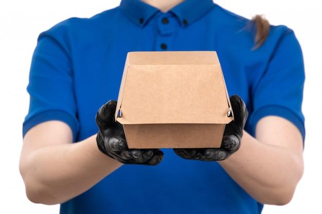 Uma jovem mensageira de frente com uma máscara preta de uniforme azul e luvas segurando um pacote de entrega de comida