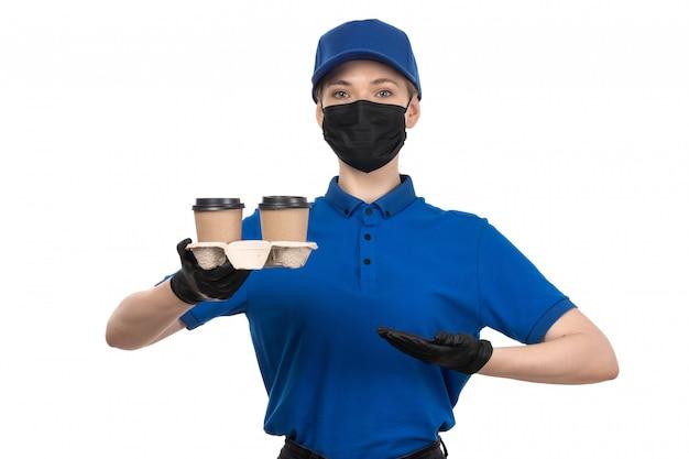 Uma jovem mensageira de frente com uma máscara preta de uniforme azul e luvas segurando xícaras de café