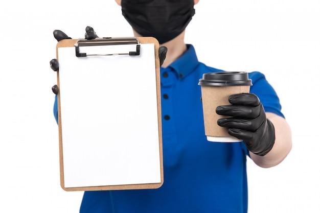 Uma jovem mensageira de frente com uma máscara preta uniforme azul e luvas segurando uma xícara de café e um bloco de notas