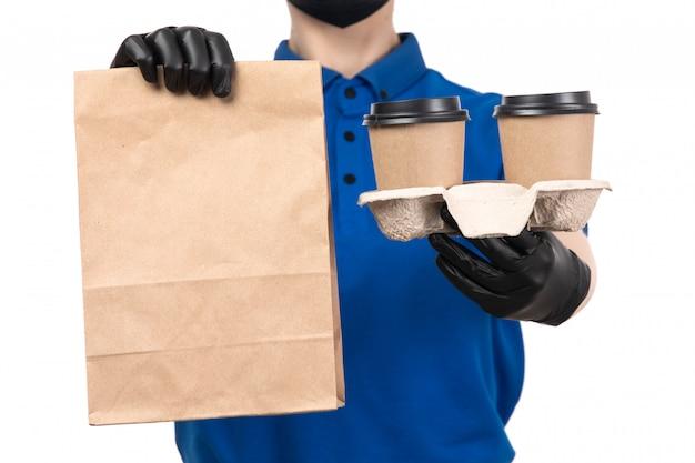 Uma jovem mensageira de frente para o uniforme azul com máscara preta e luvas segurando xícaras de café e um pacote