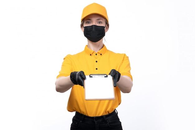 Uma jovem mensageira de frente para o uniforme com luvas pretas de uniforme amarelo e máscara preta segurando um bloco de notas para assinar
