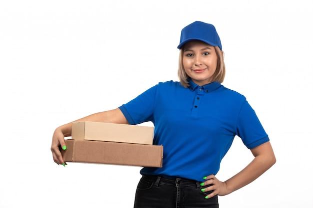 Uma jovem mensageira de uniforme azul segurando um pacote de entrega de comida com um sorriso no rosto