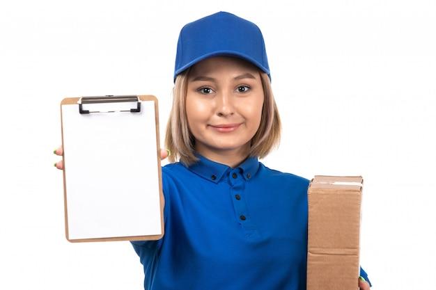 Uma jovem mensageira de uniforme azul segurando um pacote de entrega de comida e um bloco de notas para assinaturas