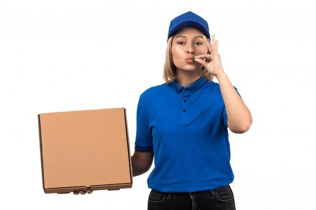 Uma jovem mensageira de uniforme azul segurando um pacote de entrega de comida