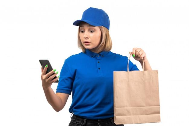 Uma jovem mensageira de uniforme azul segurando um telefone e um pacote de entrega de comida