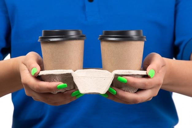 Uma jovem mensageira de uniforme azul segurando xícaras de café