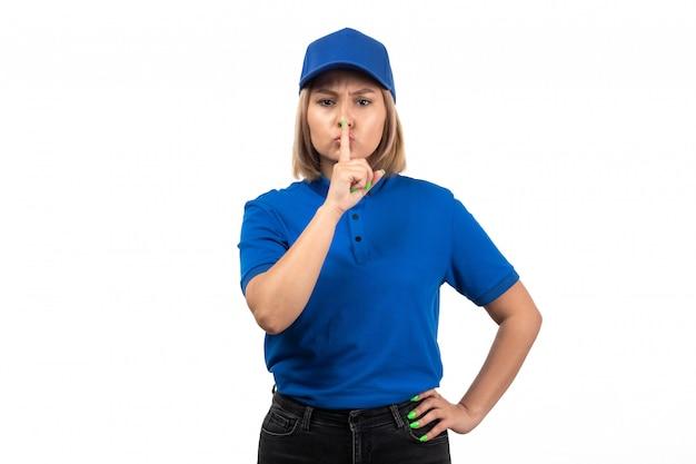 Uma jovem mensageira de uniforme azul, vista frontal, apenas posando e mostrando o sinal de silêncio