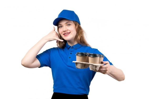 Uma jovem mensageira de uniforme segurando xícaras com café sorrindo e mostrando a pose da ligação