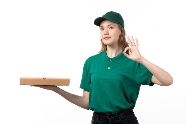 Uma jovem mensageira de uniforme verde segurando uma caixa de entrega de pizza e mostrando a placa de tudo bem