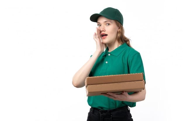 Uma jovem mensageira de uniforme verde, sorrindo, segurando pacotes com comida sussurrando
