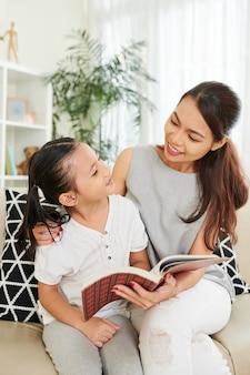 Uma jovem mesquinha e sua filha pré-adolescente lendo um livro juntas quando estão sentadas no sofá da sala de estar