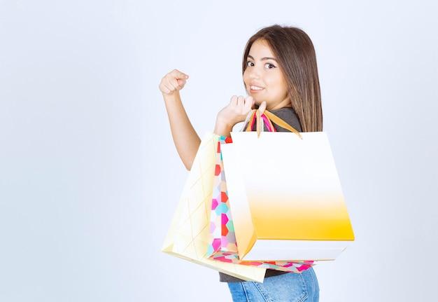 Uma jovem modelo carregando suas sacolas de compras e apontando para elas.