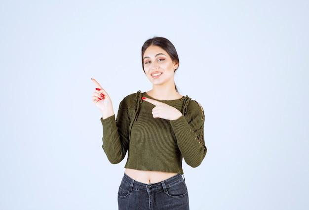Uma jovem modelo com blusa verde apontando para uma parede branca