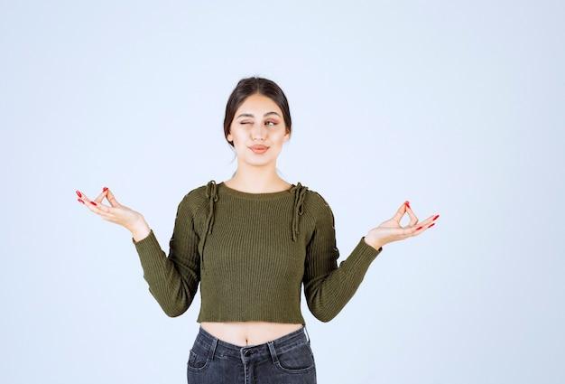 Uma jovem modelo com blusa verde meditando sobre uma parede branca