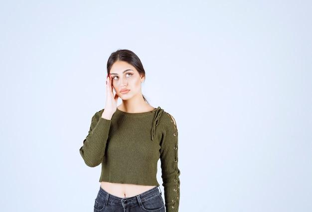Uma jovem modelo de blusa verde pensando em algo sobre uma parede branca