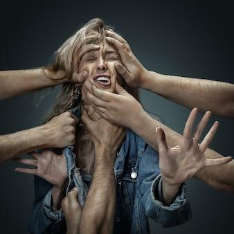 Uma jovem modelo feminina cercada por mãos masculinas como seus próprios pensamentos ou problemas na parede escura