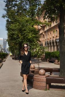 Uma jovem modelo mulher em um vestido preto e óculos escuros andando pela calçada e desfrutando de um sol ...