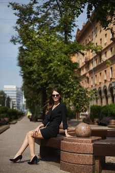 Uma jovem modelo mulher em um vestido preto e óculos escuros, sentada no banco na rua da cidade em uma soma ...