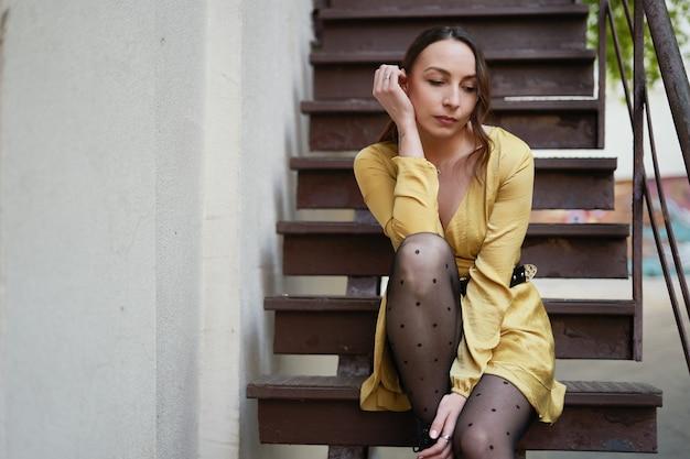 Uma jovem moderna em vestido amarelo posando na escada
