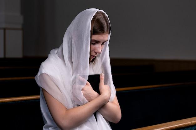 Uma jovem modesta garota com um lenço na cabeça e uma bíblia nas mãos dela está sentado na igreja e rezando.