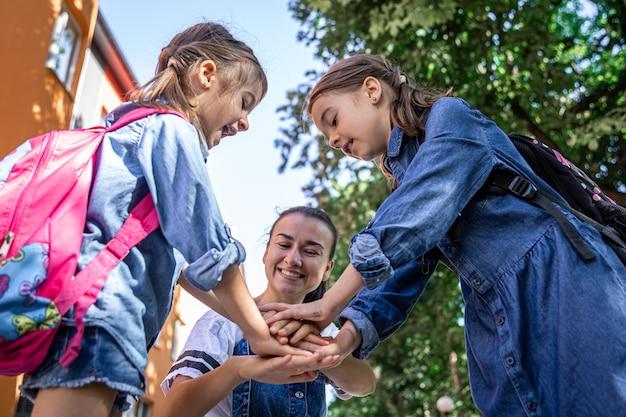 Uma jovem moralmente apóia as filhas de mãos dadas incentiva os filhos, a mãe acompanha os alunos à escola.