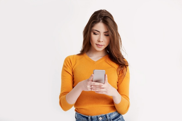 Uma jovem morena bonita se comunica com os amigos usando um telefone celular