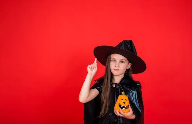 Uma jovem morena com uma fantasia de bruxa e um chapéu segura uma abóbora e mostra sua mão sobre um fundo vermelho com uma cópia do espaço