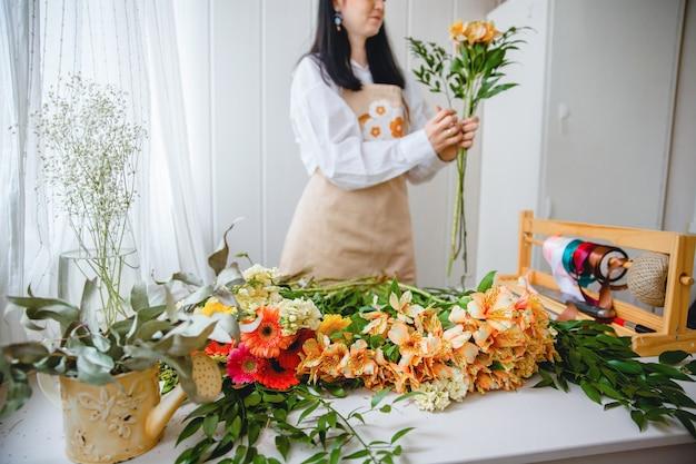 Uma jovem morena de avental no processo de criação de um buquê em estilo rústico em sua floricultura
