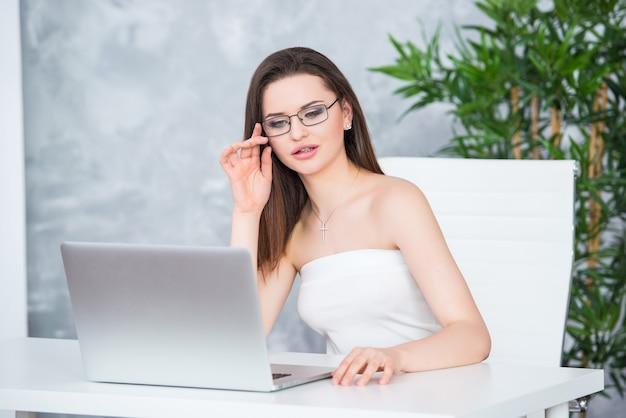 Uma jovem morena de óculos em um vestido branco está sentada no escritório à mesa. mulher trabalha no laptop. visão subnormal ou acessório de moda.