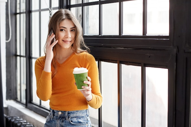 Uma jovem morena de suéter amarelo fica ao lado da janela com uma xícara de café e um telefone na mão, falando ao telefone