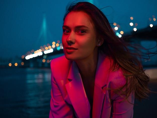 Uma jovem morena elegante nas luzes da iluminação neon da cidade à noite