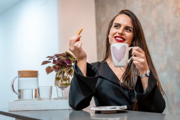 Uma jovem morena em um café tomando café