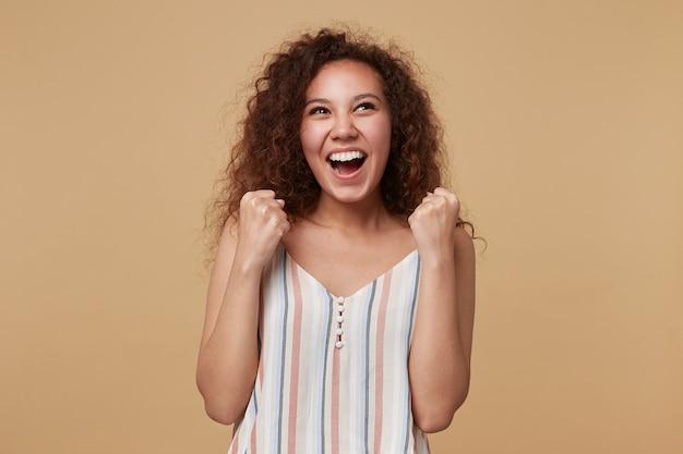 Uma jovem morena encaracolada feliz olhando animadamente para cima e erguendo os punhos alegremente, usando uma blusa listrada em pé no bege