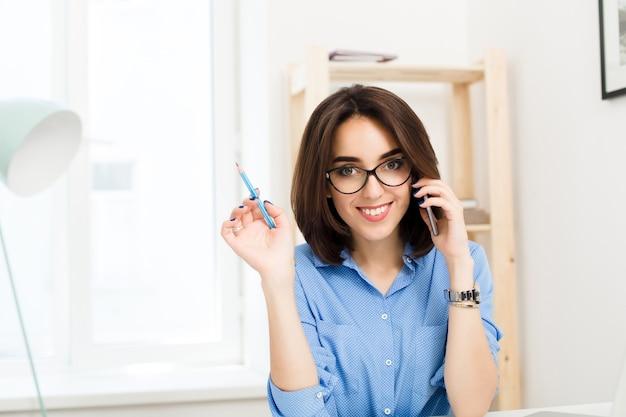 Uma jovem morena está sentada à mesa no escritório. ela está falando ao telefone e sorrindo para a câmera.