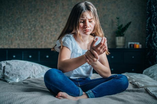 Uma jovem morena está sentada em uma cama no quarto dela. ela segura uma mão dolorida.