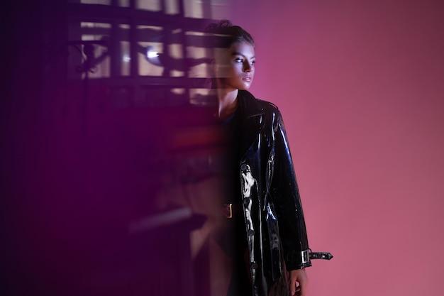 Uma jovem morena estilosa com uma capa de chuva de látex sobre um macacão preto, uma imagem da moda noir em uma misteriosa silhueta borrada vai para as sombras
