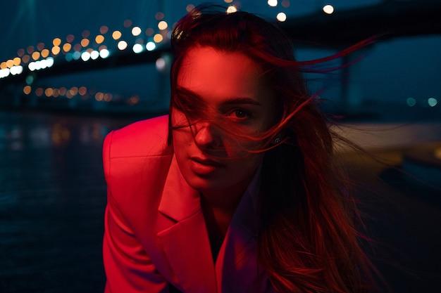 Uma jovem morena estilosa nas luzes da cidade à noite, iluminação neon,