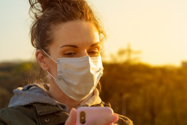 Uma jovem morena européia em uma máscara de proteção médica usa seu smartphone fora por do sol à noite.