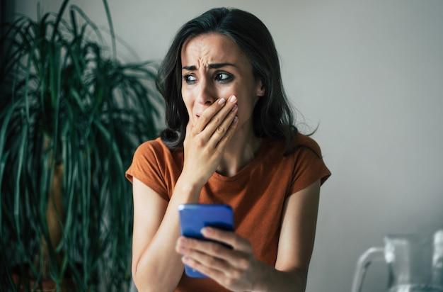 Uma jovem morena frustrada e triste está chorando com o smartphone nas mãos enquanto está sentada na cadeira do apartamento