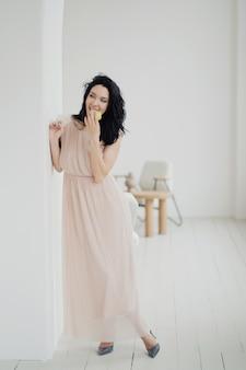 Uma jovem morena posa para a câmera comendo uma maçã em um novo e elegante vestido bege e sapatos elegantes com salto. roupa de férias