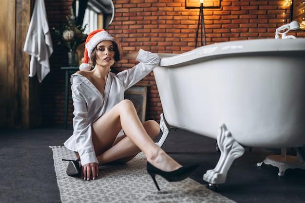 Uma jovem morena posando no chão perto da banheira com chapéu de natal, camisa branca e salto alto preto.