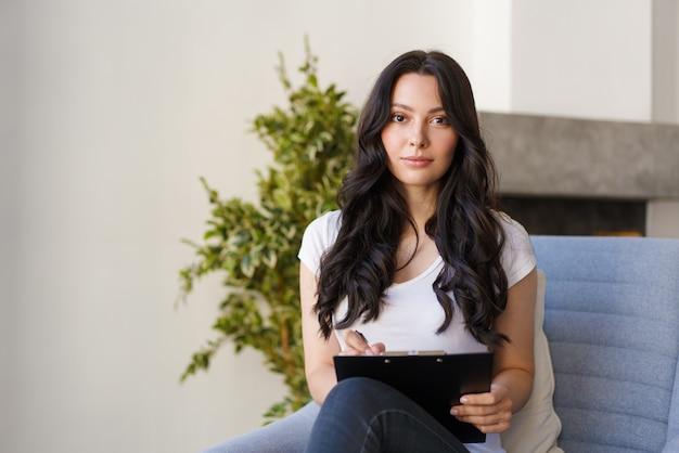 Uma jovem morena preenche as informações do questionário que a mulher olha para a câmera e