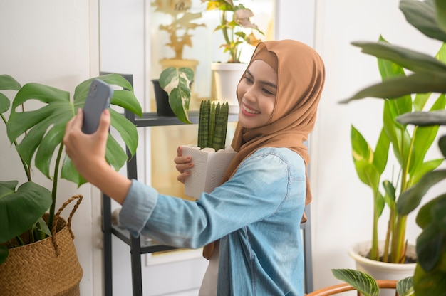 Uma jovem muçulmana feliz tirando uma selfie com suas plantas e fazendo videochamada em casa