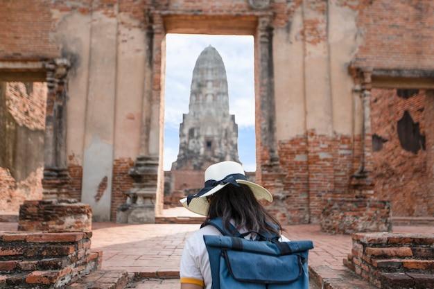 Uma jovem mulher anda no templo velho em phra nakhon si ayutthaya, tailândia em um dia de relaxamento.