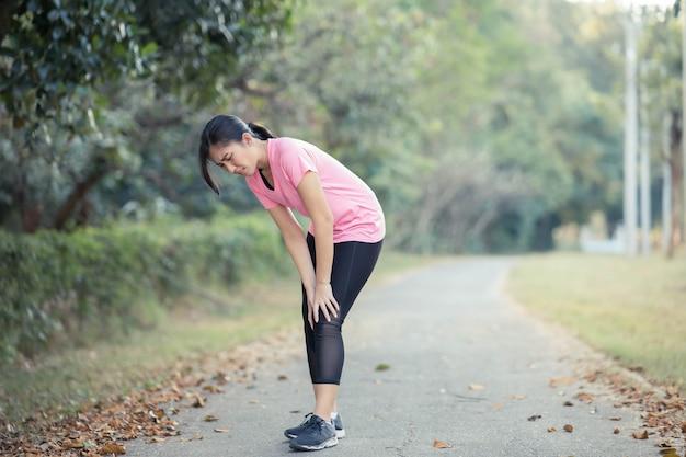 Uma jovem mulher asiática doeu os joelhos depois de correr.