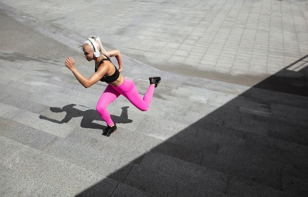 Uma jovem mulher atlética em camisa e fones de ouvido brancos malhando ouvindo música ao ar livre na rua.