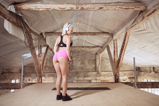 Uma jovem mulher atlética em fones de ouvido brancos malhando ouvindo música em uma construção abandonada. faça exercícios com a corda. conceito de estilo de vida saudável, esporte, atividade, perda de peso.