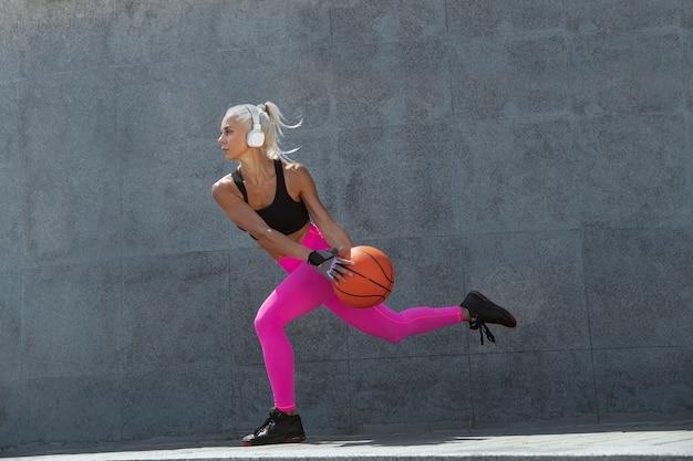 Uma jovem mulher atlética em uma camisa e fones de ouvido brancos malhando ouvindo música na rua ao ar livre.