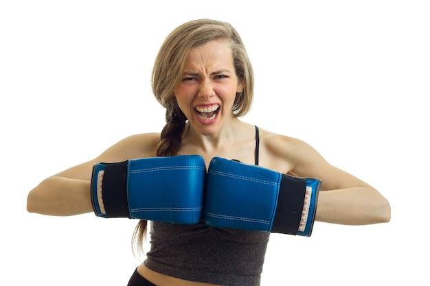 Uma jovem mulher atlética grita e segura as mãos em luvas de boxe antes de um close-up isolado na parede branca